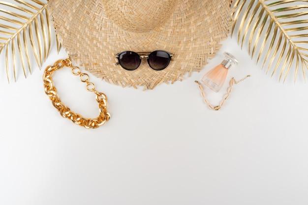 Vista superiore del cappello e degli occhiali da sole di paglia su fondo bianco