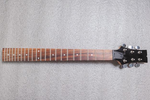 Vista superiore del collo di chitarra polverosa. prima di macinare i tasti.