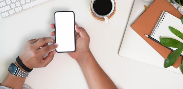 Vista superiore del colpo potata delle mani dell'uomo d'affari facendo uso del modello dello smartphone alla scrivania bianca