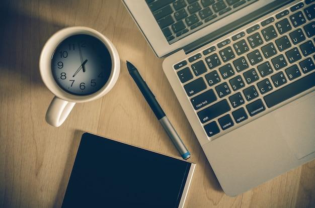 Vista superiore del computer portatile, blocco note e tazza di caffè che ha mostrato il tempo