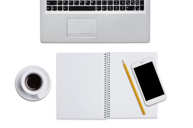 Vista superiore del computer portatile, del blocco note a spirale con la matita, dello smart phone e della tazza di caffè isolati sopra fondo bianco. posto di lavoro dell'uomo d'affari