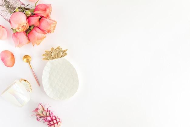 Vista superiore del concetto festivo della regolazione della tavola. piatto di ananas e posate rosa oro su bianco con fiori di rose.