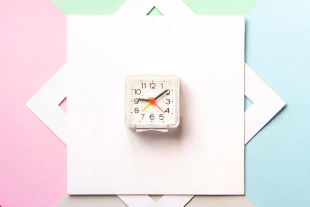 Vista superiore del concetto minimalista con gli orologi d'annata nel telaio vuoto bianco isolato sulla superficie f di colore