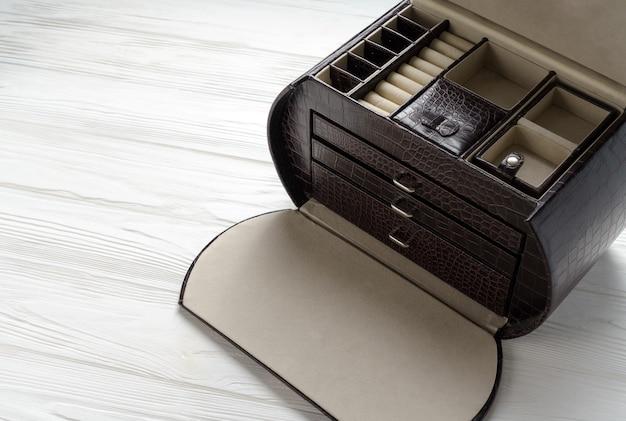 Vista superiore del contenitore di gioielli di cuoio marrone vuoto sulla tavola di legno bianca