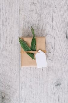 Vista superiore del contenitore di regalo avvolto marrone con etichetta e foglie verdi sulla tavola di legno