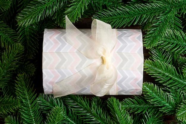Vista superiore del contenitore di regalo festivo decorato con rami di abete verde