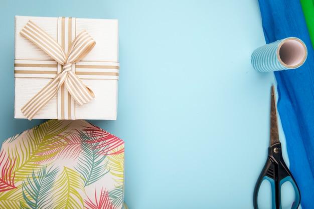 Vista superiore del contenitore di regalo legato con l'arco e le forbici con i rotoli di carta variopinta su fondo blu con lo spazio della copia