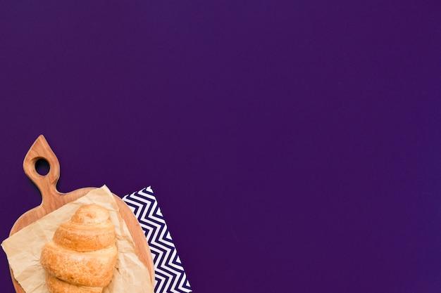 Vista superiore del croissant sul tagliere e carta artigianale su sfondo blu oltremare con spazio di copia.