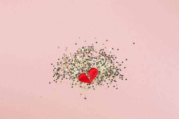 Vista superiore del cuore spezzato di coriandoli stelle dorate