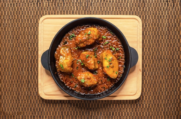 Vista superiore del curry piccante e caldo del pesce bengalese. cibo indiano. pesce al curry con peperoncino rosso, foglia di curry, latte di cocco. cucina asiatica.