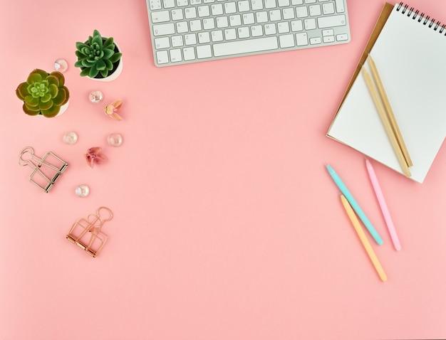 Vista superiore del desktop moderno ufficio donna rosa con blocco note vuoto