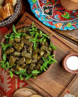 Vista superiore del dolma tradizionale in foglie di vite con yogurt acido su un tavolo di legno