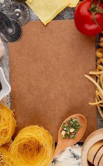 Vista superiore del foglio di cartone e pasta cruda italiana di diversi tipi e forme con pomodori freschi e coltello a rulli taglierina su sfondo nero
