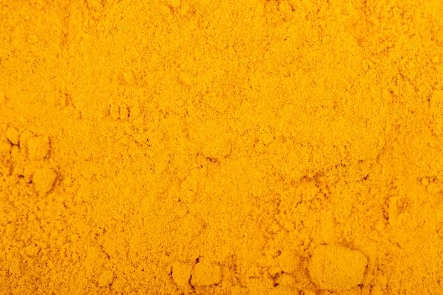 Vista superiore del fondo e della struttura della polvere di curcuma