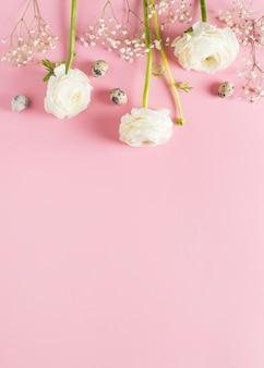 Vista superiore del fondo piano rosa di disposizione dei fiori felici di pasqua