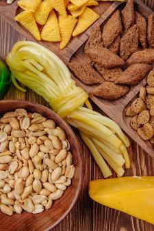 Vista superiore del formaggio a corde salato dei cracker del pane dei coni del cereale degli spuntini della birra e delle arachidi salate su legno rustico