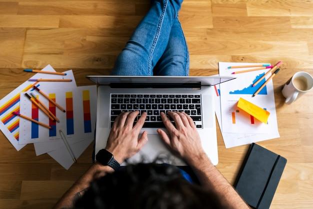 Vista superiore del giovane che lavora con il suo computer portatile dal suo salotto. resta a casa, lavora da casa concetto