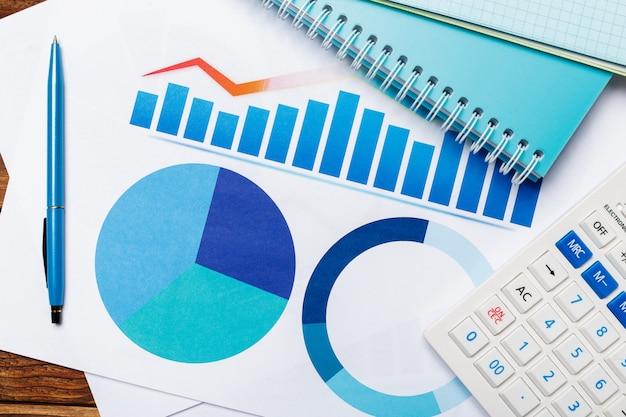 Vista superiore del grafico delle carte d'ufficio sulla tavola di legno con il calcolatore