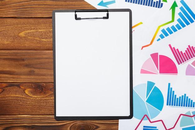 Vista superiore del grafico delle carte d'ufficio sulla tavola di legno con la lavagna per appunti vuota