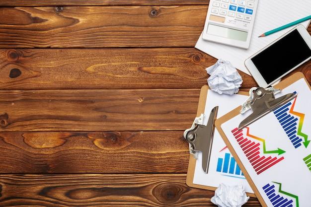Vista superiore del grafico o del grafico delle carte d'ufficio su fondo di legno