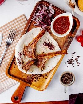 Vista superiore del kebab delle costole dell'agnello con le cipolle rosse su un bordo di legno