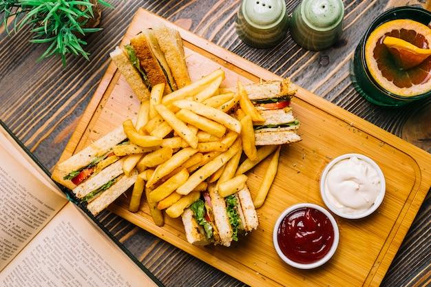 Vista superiore del ketchup della maionese delle patate fritte del cetriolo del pomodoro del pollo del pane tostato del panino di club