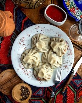 Vista superiore del khinkaliwith georgiano tradizionale sumakh e salsa piccante su un piatto bianco