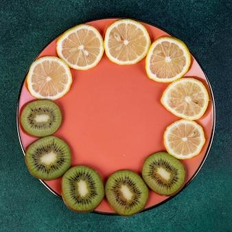 Vista superiore del kiwi e del limone affettati sul piatto su verde scuro