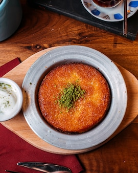 Vista superiore del kunefe turco tradizionale del dessert con polvere di pistacchio su una tavola di legno