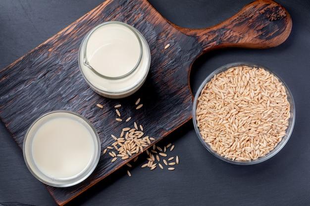 Vista superiore del latte di avena sano in bottiglia di vetro e semi di avena e vetro sulla ciotola di vetro