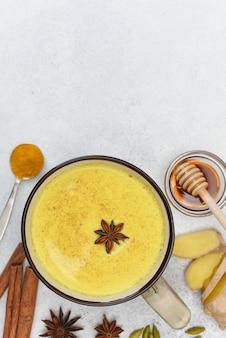 Vista superiore del latte di curcuma. latte dorato in tazza con anice stellato e spezie intorno. curcuma, cannella, zenzero, miele, anice stellato, cardamomo.