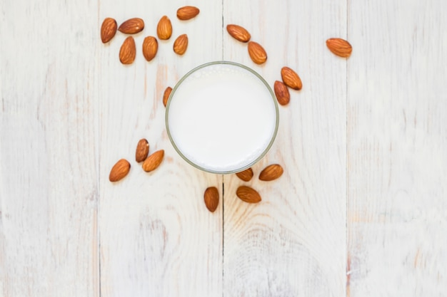 Vista superiore del latte di mandorle fatto in casa in un bicchiere e noci sparse su fondo di legno. copia spazio.