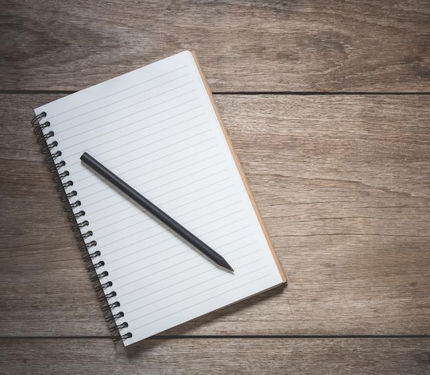 Vista superiore del libro bianco e della matita nera sul vecchio fondo di legno della plancia