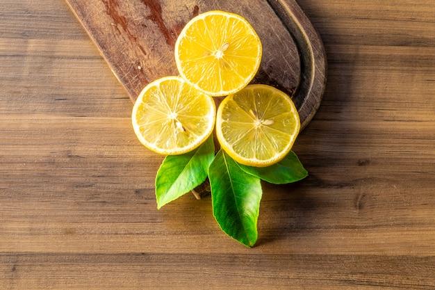Vista superiore del limone e delle foglie verdi sulla tavola di legno
