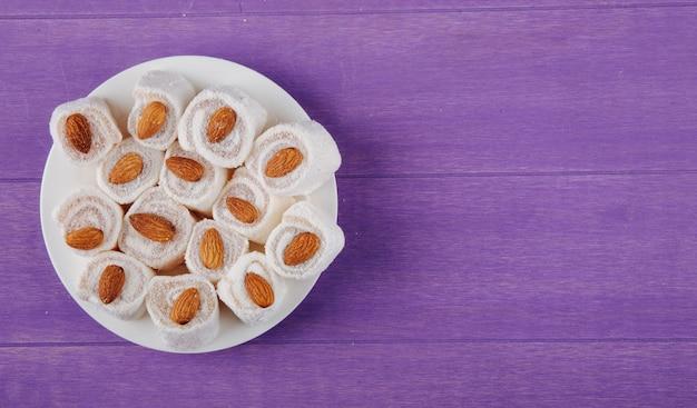 Vista superiore del lokum del rahat di delizie turche su un piatto bianco su superficie di legno porpora con lo spazio della copia