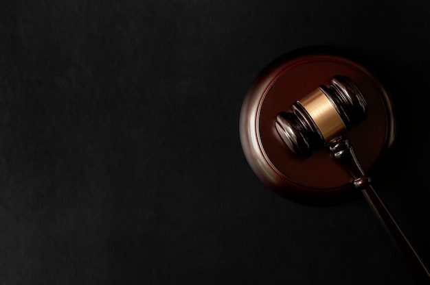 Vista superiore del martelletto del giudice in legno e blocco suono sul tavolo superiore in pelle nera.