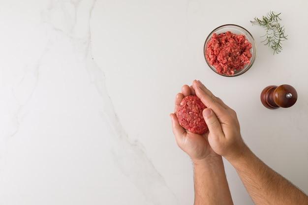 Vista superiore del maschio stampaggio a mano un hamburger in un tavolo di marmo, una ciotola di vetro con carne, smerigliatrice di pepe in legno e rosmarino con spazio per il testo