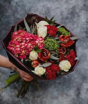 Vista superiore del mazzo con le rose di colore bianco i tulipani rossi l'ortensia e la pianta rosa