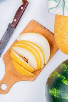 Vista superiore del melone affettato sul tagliere con il coltello e quello intero con l'anguria su fondo bianco