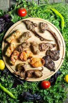 Vista superiore del mix di kebab alla griglia su un piatto di legno su erbe fresche