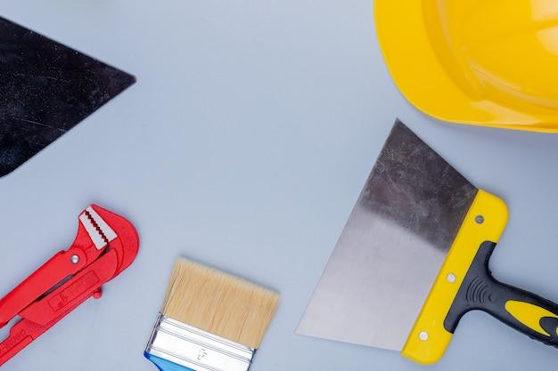 Vista superiore del modello dall'insieme degli strumenti della costruzione come pennello della spatola del casco di sicurezza della chiave stringitubo e coltello di mastice su fondo grigio