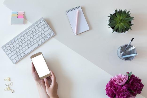 Vista superiore del modello del telefono cellulare con lo schermo bianco dello spazio della copia, disposizione piana, concetto femminile dell'area di lavoro per la scrivania della donna