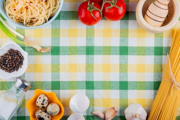 Vista superiore del mortaio di legno e delle quaglie dei pomodori freschi crudi e cotti della pasta degli spaghetti sulla tovaglia