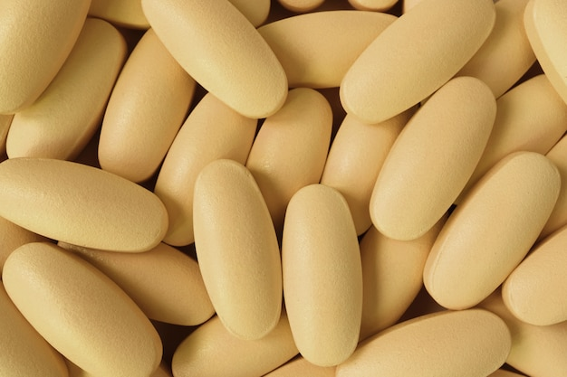Vista superiore del mucchio di pillole a forma di ovale giallo cremoso per priorità bassa