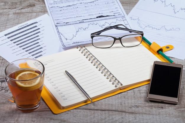 Vista superiore del notebook aperto, occhiali, una tazza di tè, penna e smartphone su un tavolo di legno