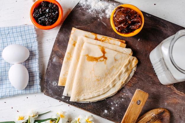 Vista superiore del pancake russo tradizionale della prima colazione con la salsa e il latte dell'ostruzione su un tagliere di legno