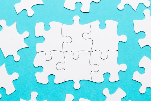 Vista superiore del pezzo di puzzle bianco su sfondo blu