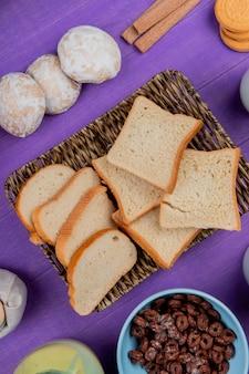 Vista superiore del piatto della merce nel carrello delle fette del pane bianco con i pan di zenzero dei cereali dei biscotti al latte condensato intorno sulla tavola porpora