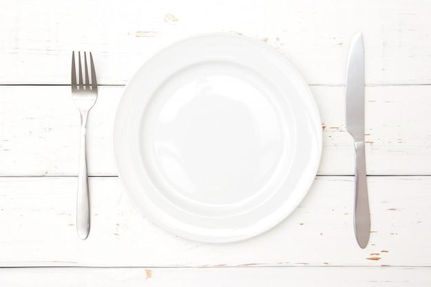 Vista superiore del piatto, forchetta e coltello su fondo di legno