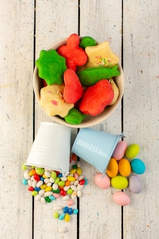 Vista superiore del piatto interno multicolore formato differente formato delizioso variopinto dei biscotti con le caramelle